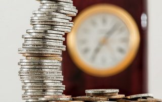 Stack of coins in front of a clock, counting value of business